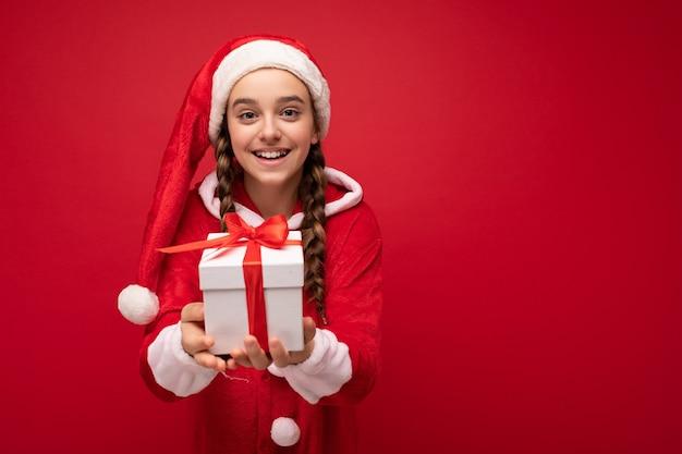 Foto des schönen glücklichen lächelnden brünetten mädchens lokalisiert über der roten hintergrundwand, die weihnachtsmann-anzug hält, der weiße geschenkbox mit rotem band hält und kamera betrachtet. speicherplatz kopieren