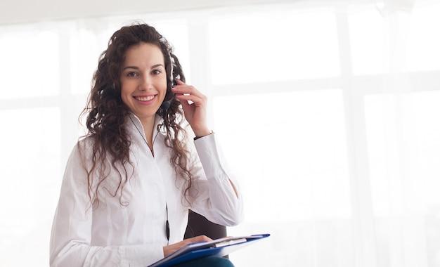 Foto des schönen jungen call-center-betreibers, der über weißem hintergrund steht