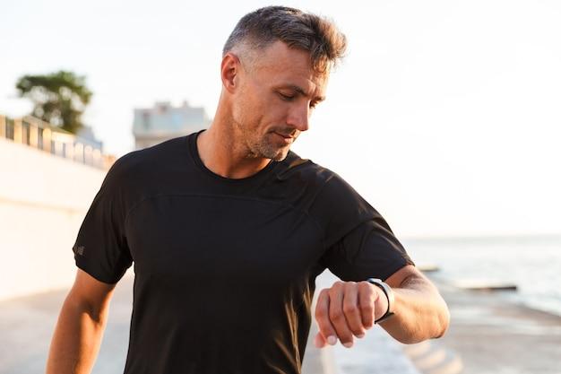 Foto des schönen kaukasischen mannes 30s im trainingsanzug, der entlang promenade, nahe meer während des sonnenaufgangs geht und intelligente armbanduhr betrachtet
