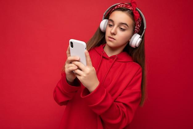 Foto des schönen konzentrierten ernsten brünetten mädchens, das roten hoodie auf rotem hintergrund isoliert trägt