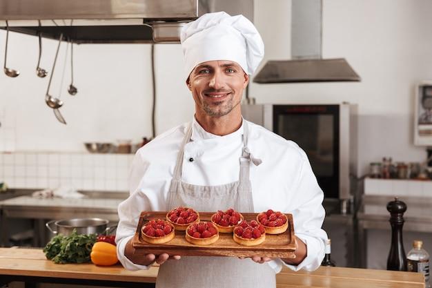 Foto des schönen männlichen chefs in der weißen uniform, die platte mit kuchen hält