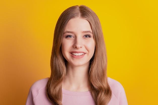 Foto des schönen positiven fröhlichen mädchens glänzendes weißes lächeln auf gelbem hintergrund