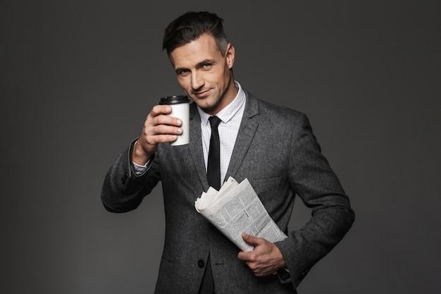 Foto des schönen sachlichen mannes gekleidet in geschäftskostüm, der kaffee zum mitnehmen im büro trinkt und zeitung liest, lokalisiert über graue wand