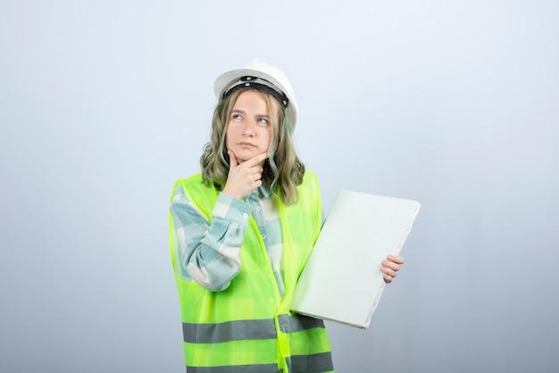 Foto des schönen weiblichen industriearbeiters, der leere leinwand und denken hält. hochwertiges foto