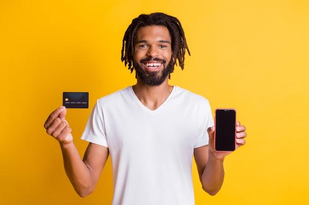 Foto des schwarzen kerls, der den leeren raum des debitkartentelefons präsentiert, trägt ein weißes t-shirt, das isoliert gelber farbhintergrund ist