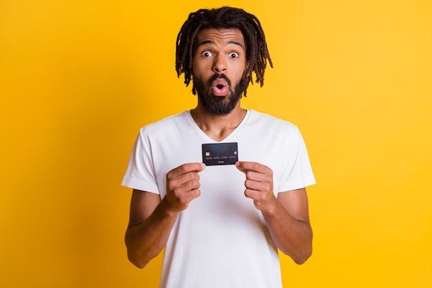 Foto des schwarzen kerls, der kreditkarte präsentiert überraschter ausdruck trägt weißes t-shirt isoliert gelber hintergrund