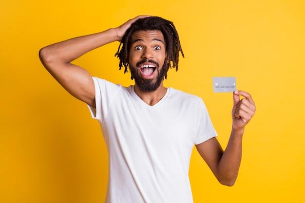 Foto des schwarzen kerls handkopf halten kreditkarte offener mund tragen weißes t-shirt isoliert gelber hintergrund