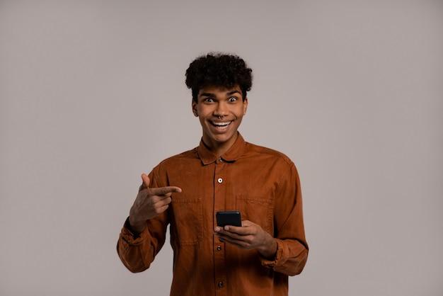 Foto des schwarzen mannes hält smartphones und zeigt darauf, sieht sehr erstaunt aus. mann trägt hemd, isolierter grauer farbhintergrund.