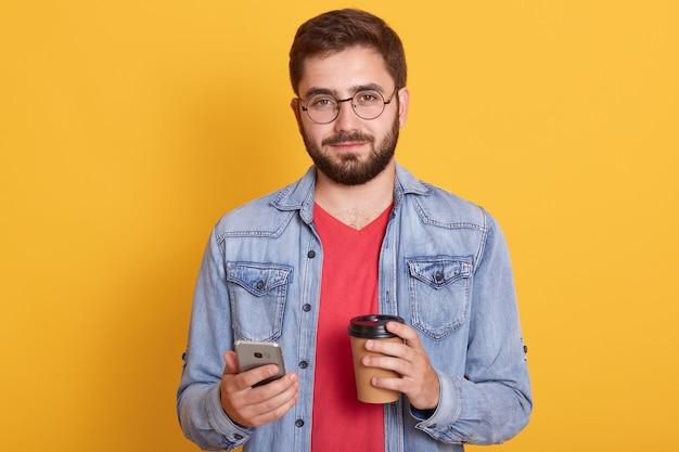 Foto des selbstbewussten gut aussehenden jungen mannes, der pappbecher mit kaffee und smartphone hält und jeansjacke, brille und t-shirt trägt