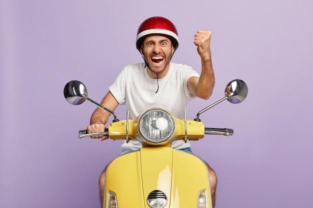 Foto des selbstbewussten kerls mit helm, der gelben roller fährt