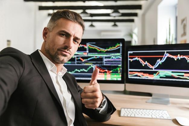 Foto des selbstbewussten mannes 30s, der anzug trägt, der selfie nimmt, während im büro am computer mit grafiken und diagrammen am bildschirm arbeitet