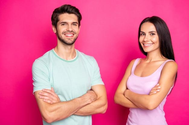 Foto des selbstbewussten paares kerl und dame, die mit verschränkten armen zuverlässige arbeiter stehen, tragen freizeitkleidung lokalisierten lebendigen rosa farbhintergrund