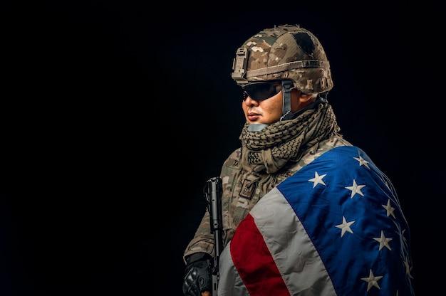 Foto des soldaten, der die usa-flagge im hintergrund hält. special force us-soldat oder militärunternehmer, die gewehr halten. bild im hintergrund. soldat, armee, krieg, waffen und technologiekonzept.