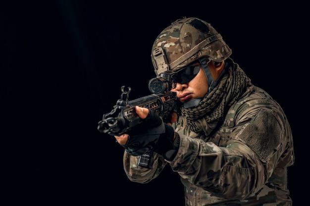 Foto des soldaten im schwarzen hintergrund. special forces us-soldat oder private militärunternehmen mit gewehr. bild auf schwarzem hintergrund. soldat, armee, krieg, waffen und technologiekonzept.
