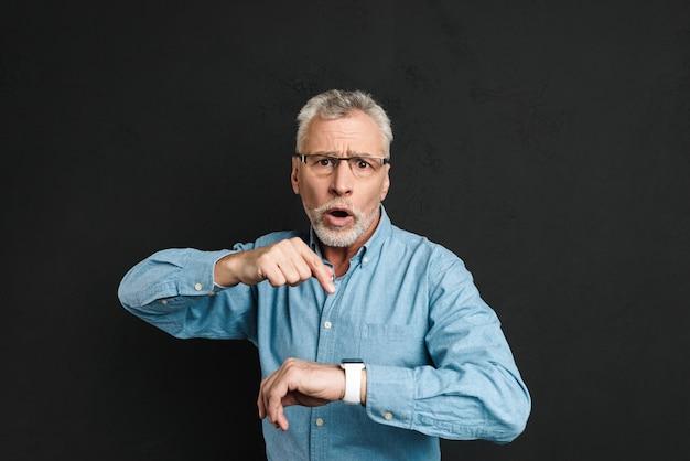 Foto des straffen herrn 60er jahre mit grauem haar, das eine brille trägt, die finger auf seine armbanduhr mit schock zeigt, lokalisiert über schwarzer wand