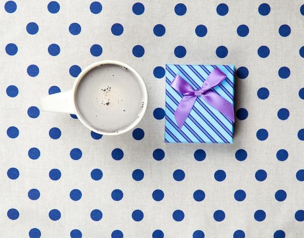 Foto des tasse kaffees und des niedlichen geschenks auf dem wunderbaren weiß punktierte hintergrund in der popkunstart