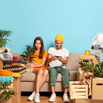 Foto des traurigen jungen paares, das auf der couch sitzt, umgeben von kisten