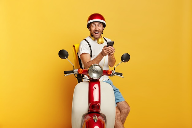 Foto des überglücklichen gutaussehenden männlichen fahrers auf roller mit rotem helm