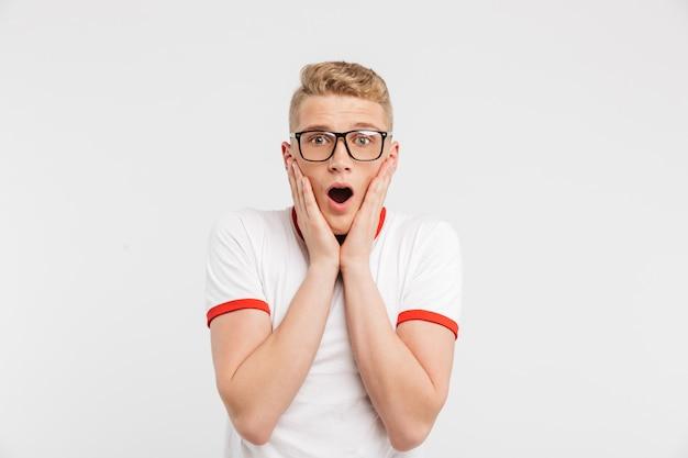 Foto des überraschten kerls in der brille, die schreit und gesicht in der angst oder im schock auf weiß isoliert greift