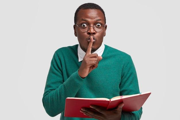 Foto des überraschten männlichen lehrers hält zeigefinger über mund, zeigt shush-geste, liest lehrbuch, bittet um ruhe, trägt brille