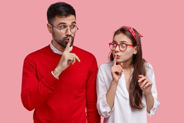 Foto des überraschten weiblichen und männlichen klatsches zusammen, machen schweigegeste, erzählen geheime informationen, schauen sich mit verschwörung an