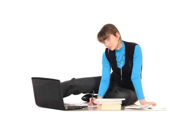Foto des ungezogenen studentenmädchens mit braunen haaren im schwarzen anzug mit personal computer-aufstellung, lokalisiert auf weiß