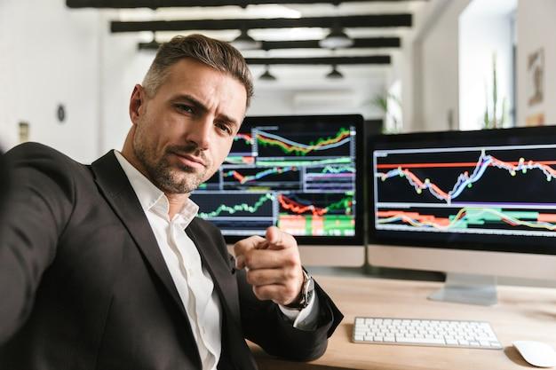 Foto des unrasierten mannes 30s, der anzug trägt, der selfie nimmt, während im büro am computer mit grafiken und diagrammen am bildschirm arbeitet