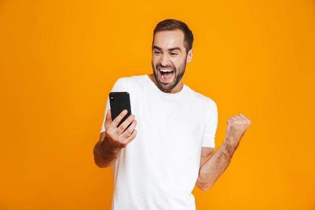 Foto des unrasierten mannes 30s in der freizeitkleidung, die smartphone lächelt und hält, lokalisiert