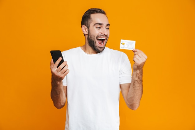 Foto des unrasierten mannes 30s in der freizeitkleidung, die smartphone und kreditkarte hält, lokalisiert