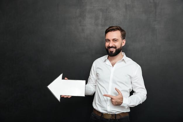 Foto des unrasierten mannes lächelnd und leeren sprachepfeilzeiger halten, der beiseite über dunkelgrauen wandkopienraum verweist