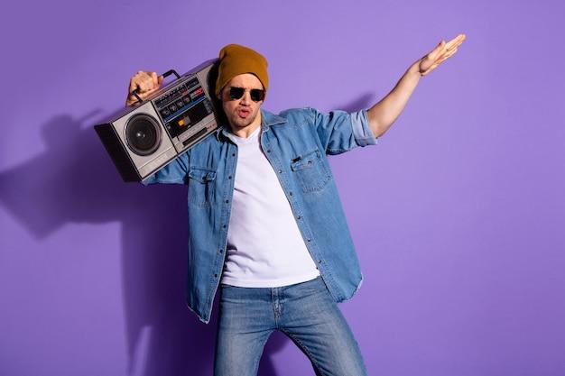 Foto des unvorsichtigen mannes, der mit lauter bassmusik tanzt, die jeans-jeanshemd weiß trägt, lokalisiert über lila violettem lebendigem farbhintergrund