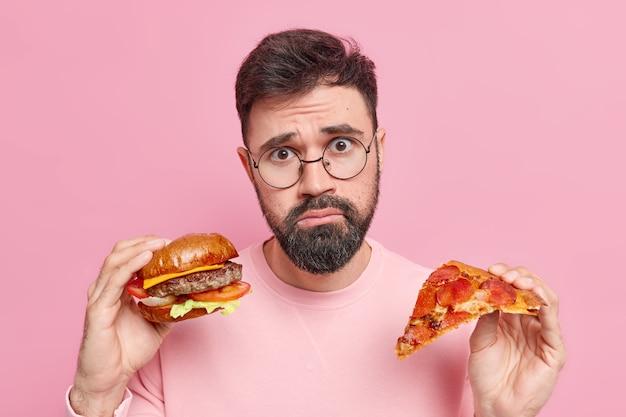 Foto des unzufriedenen bärtigen mannes kann das essen von fast food nicht ablehnen, hält köstlichen hamburger und ein stück leckere pizza sieht unglücklich aus, hat ungesunde ernährung