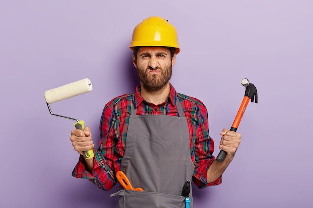 Foto des unzufriedenen männlichen baumeisters grinst gesicht mit unglücklichem ausdruck