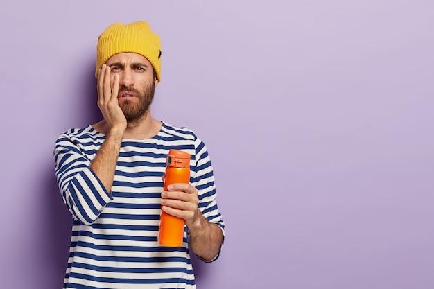 Foto des unzufriedenen mannes hält hand auf wange, trägt flasche mit kaffee oder tee, hat schläfrigen müden ausdruck, trägt freizeitkleidung