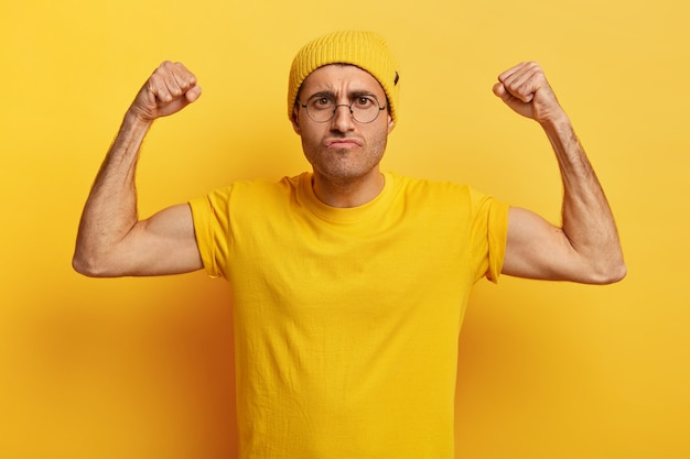 Foto des unzufriedenen mannes mit wütendem gesichtsausdruck, hebt hände, ballt fäuste
