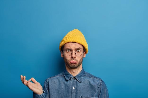 Foto des verärgerten verwirrten mannes hebt handfläche an, sieht mit gestörtem traurigem ausdruck aus, trägt gelben hut, jeanshemd
