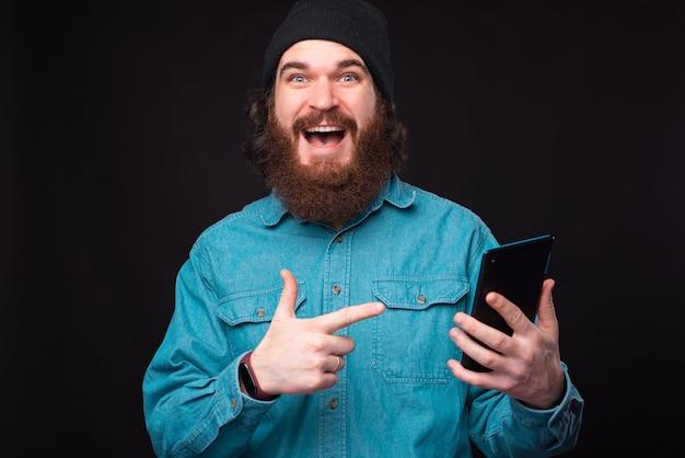 Foto des verblüfften bärtigen hipster-mannes, der auf tablette zeigt