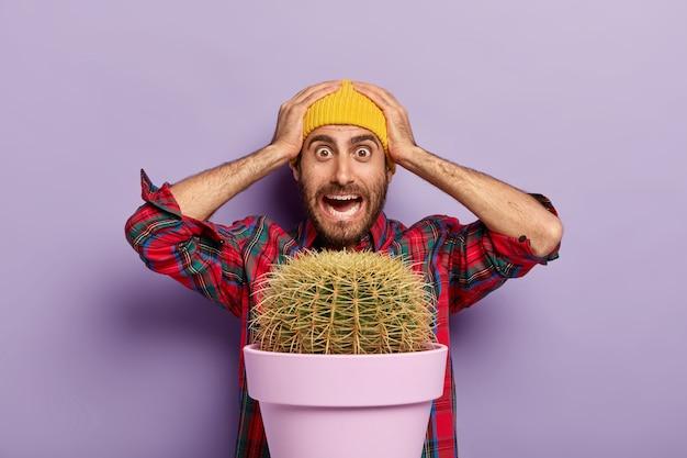 Foto des verlegenen betäubten kaukasischen mannes hält hände auf kopf, starrt mit schock, gekleidet in kariertes hemd und gelben hut, steht hinter topf des großen kaktus, isoliert über lila hintergrund