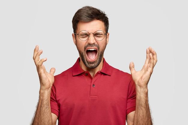 Foto des verrückten unrasierten jungen mannes gestikuliert wütend, ruft in der negativität aus
