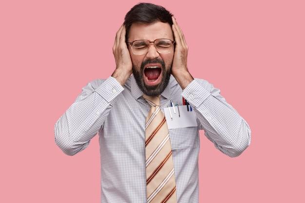 Foto des verzweifelten genervten bärtigen mannes hält hände auf dem kopf, schreit laut, hält handflächen auf den ohren, öffnet den mund, schließt die augen, fühlt sich deprimiert