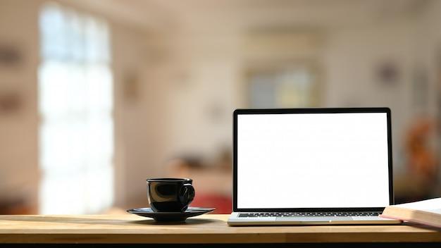 Foto des weißen leeren bildschirmlaptops, der schwarzen kaffeetasse und der untersetzer auf dem hölzernen schreibtisch über unscharfem modernem café