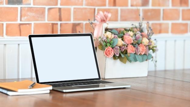 Foto des weißen leeren bildschirmlaptops, des notizbuchs, des stiftes und des rosenstraußes in dem weißen plastikkorb, der auf den holztisch mit betonwand als hintergrund setzt.