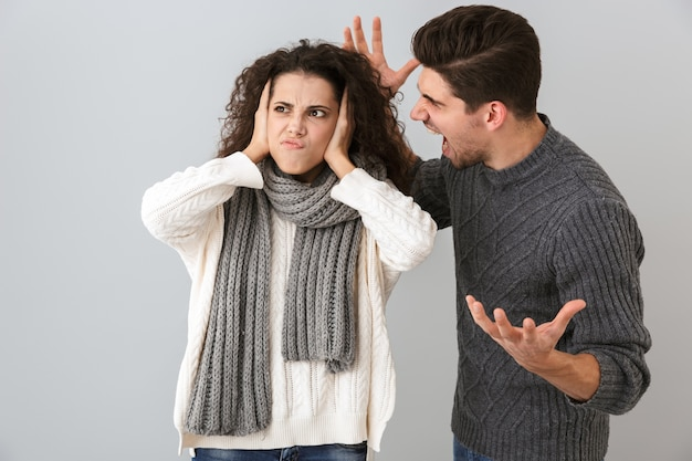 Foto des wütenden mannes und der wütenden frau, die einander von angesicht zu angesicht schreiend, lokalisiert über graue wand schreien