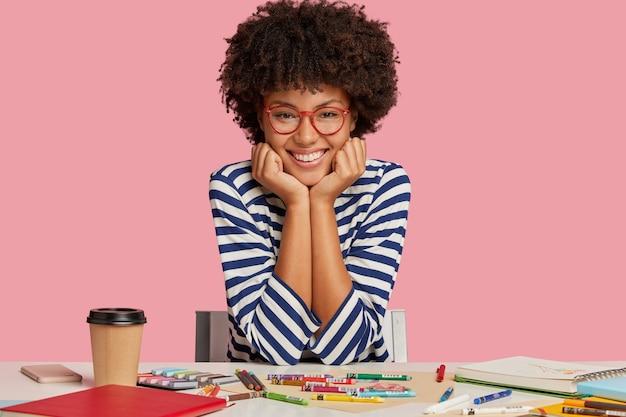 Foto des zufriedenen lächelnden dunkelhäutigen grafikdesigners, der in guter stimmung ist