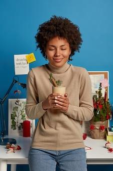 Foto des zufriedenen weiblichen modells genießt das trinken des traditionellen weihnachtsgetränks, des klassischen wintergetränks, bereit, weihnachten zu feiern, posiert im arbeitszimmer in der nähe des desktops, schließt die augen und lächelt sanft
