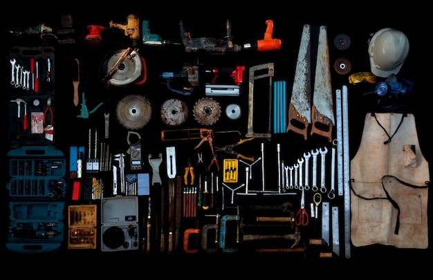 Foto draufsicht eine riesige sammlung von arbeitshand- und elektrowerkzeugen, viele davon für holz auf isolierter schwarzer oberfläche