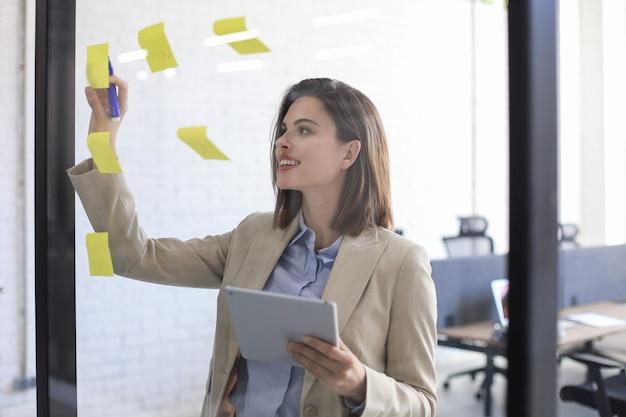 Foto durch das glas attraktiver geschäftsfrau-postaufkleber auf glas im büro und schreiben auf ihnen.