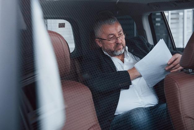 Foto durch das glas. papierkram auf dem rücksitz des autos. senior geschäftsmann mit dokumenten