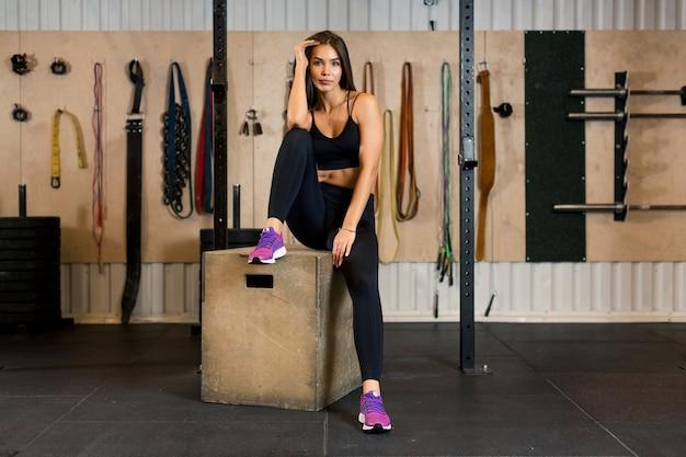 Foto eine sportlerin, die auf einem holzwürfel in einem fitnessstudio nach einem training sitzt