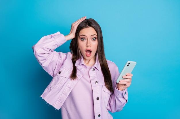 Foto einer attraktiven angstdame, die das telefon mit offenem mund hält, liest corona-virus-nachrichten im internet